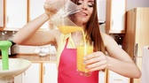 maker : Woman young housewife in kitchen making fresh orange juice in juicer machine, pouring drink from jug in glass. Healthy eating, vegetarian food, dieting and people concept. 4K ProRes HQ codec