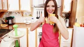 потеря в весе : Woman young housewife in kitchen at home drinking fresh homemade orange juice drink making thumb ub gesture. Healthy eating, vegetarian food, weight loss and people concept. 4K ProRes HQ codec