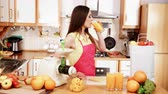 extractor : Woman young housewife in kitchen making fresh orange juice in juicer machine, drinking it from glass. Healthy eating, vegetarian food, dieting and people concept. 4K ProRes HQ codec