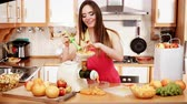 extractor : Woman young housewife in kitchen making fresh orange juice in juicer machine, preparing nutritious vitamin packed drink. Healthy eating, vegetarian food, dieting and people concept. 4K ProRes HQ codec