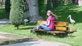 šortky : girl reading a book in a picturesque Park on the background of a living storks, Sunny day. the girl of the Asian appearance Dostupné videozáznamy