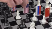 domínio : Politicians hand moves a chess piece with a flag. Conceptual photo of a political game. Retaliatory move USA Stock Footage