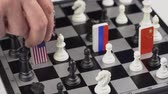 レスポンス : Politicians hand moves a chess piece with a flag. Conceptual photo of a political game. Retaliatory move Russian and USA
