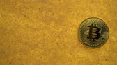 one bitcoin crypto coin on a shiny golden sand background with backlight, top view. offset effect Wideo