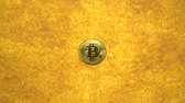 one bitcoin crypto coin on a shiny golden sand background with backlight, top view. zoom effect Wideo