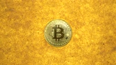 kazmak : one bitcoin crypto coin on a shiny golden sand background with backlight, top view. zoom effect Stok Video