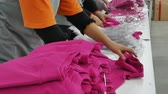 Quality control of garments in textile factory. Workers in the process of packaging textile products