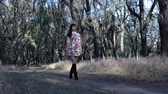 step : Beautiful slender girl in dress with long hair, walking in the park