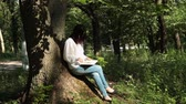 sólido : Girl sitting on a tree trunk and reading a book. Stock Footage