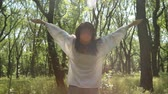 tourists : Woman raise hands in sunny forest, close-up. Smiling relaxed girl. Stock Footage