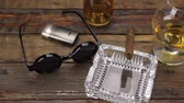 koňak : Luxurious cigar, glass of alcohol and stylish sunglasses on a vintage wooden table. Panorama.