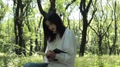 роман : Girl sits and reads a book in the park.