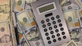 commerce : Rotation of the pen and calculator lying on the dollars. Top view. Stock Footage