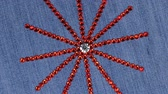 kumaş : Rotation of a star with rays made of red rhinestones. View from above.
