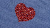tela : Rotation. Symbolic red heart made of rhinestones, a symbol of love. View from above.