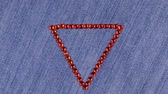 繊維 : Rotation of a triangle made of red rhinestones on denim, the triangle symbolizes completion.