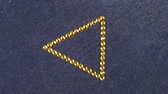 kumaş : Rotation of a triangle made of yellow rhinestones on denim, the triangle symbolizes completion.