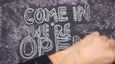 chalk board sign : Text come in were open, written with chalk on old blackboard.