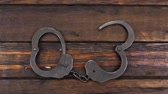 железо : Steel metallic handcuffs with keys on wooden table. Camera crane