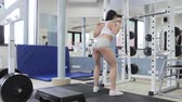 бицепс : Young woman at the gym using fitness equipment. Sporty girl raising the bar