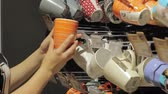 louça de barro : a female hand in a supermarket chooses cups