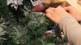madeira compensada : New Year. Female hand puts toys on the Christmas tree.