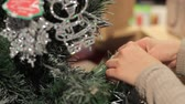 bombki : New Year. Female hand puts toys on the Christmas tree.