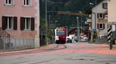 ingázó : Montbovon, Switzerland - SEP 6, 2017: the train passes right through the street of a small town Montbovon in the Gruyer district, Canton of Friborg, Switzerland. Stock mozgókép