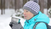 flirting : girl drinking hot hours in the winter forest Stock Footage