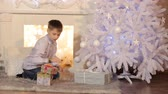 paper : Winter Holidays, Celebration and People Concept - Child Putting a Gift Under The Christmas Tree Stock Footage