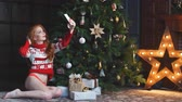 trees : Young sexy redhead girl is sitting near Christmas gifts and makes a selfie. Christmas holiday season.