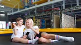 Mother And her daughter sitting on trampoline in fitness park.