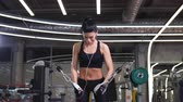 crossover : Fit woman execute exercise with exercise-machine Cable Crossover in gym Stock Footage