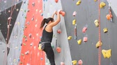 alpinista : Women climbing on a wall in an outdoor climbing center.