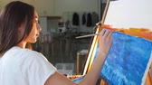 illustrateur : Woman artist painting a picture on easel with oil paints in her workshop.