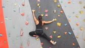 aperto : Woman practicing rock climbing on artificial wall indoors. Active lifestyle and bouldering concept.
