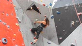альпинист : Woman practicing rock climbing on artificial wall indoors. Active lifestyle and bouldering concept.