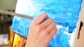 illustrateur : Woman painter drawing oil colour picture of sea surf holding palette in his hand.