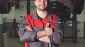 technik : Auto mechanic crossed hands and looking at camera while standing under lifting car in repair garage.