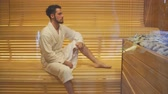 tedavi edici : Young handsome man in white robe is heated in the sauna.