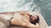 bronzeado : Free life. Portrait of the handsome and rich man sunbathing. Shot from marine private yacht. Vídeos