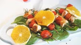 főétel : Chicken kebabs served with tomato cherry and greenery on a white chopping board on the kitchen stove, close up
