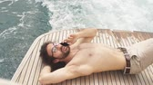 дружок : Man relaxing under the sun, lying on a wooden deck of the boat at sea. Luxury vacation on a yacht in sea