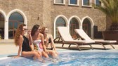 recul : Beauty and body care. Three Seductive women in stylish swimming suite, relaxing in indoor spa swimming pool at hotel. Refreshment after hot sunny day. Vidéos Libres De Droits