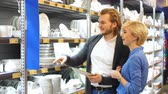 agd : Buying plates for dinner. Portrait of cute caucasian couple standing in a supermarket near household shelves thinking of choosing cookware