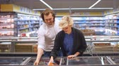 go cart : Caucasian cheerful male and female shoppers push cart with grocery products in supermarket aisle