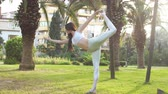 sonhador : Young woman outdoors in white sportswear relaxing between outdoor fitness classes in park, standing near palm tree, touching her gorgeous long hair.