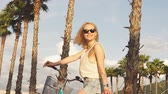 humane : Portrait of blond romantic woman vacationer in helmet and eyewear being on tropical vacation, take a bike for rent. Summer trend style, beach, riding bicycle, travel Stock Footage