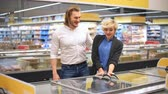 go cart : Couple in a supermarket shopping equipped with a shopping cart buying groceries and other stuff, they are looking for what they need Stock Footage