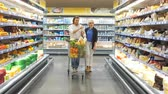 go cart : Shopping time. Positive man and woman shopping in grocery store, preparing to Christmas dinner. Couple enjoying in shopping, having fun together in shopping mall. Consumerism, love, lifestyle concept Stock Footage